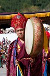 Monks in elaborate robes beat drums in the last morning procession at Thimphu tsechu. Bhutan.