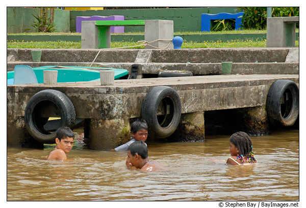 Children swimming and playing in the water. Tortuguero village, Costa Rica.