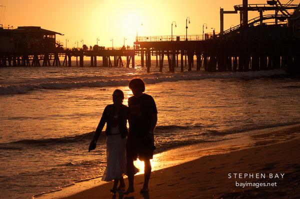 Couple at walking at sunset on Santa Monica beach.