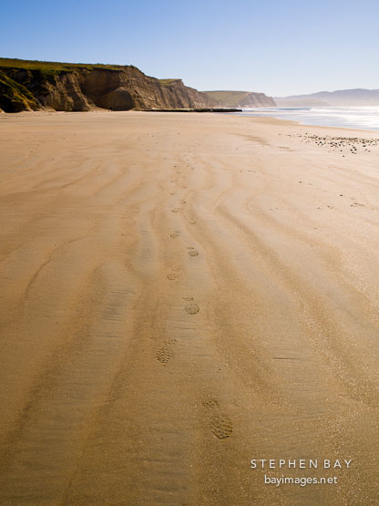 Footprints in the sand at Drake's beach. Point Reyes National Seashore, California.