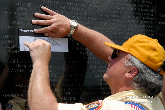 Pencil rubbing by volunteer. Vietnam Veteran's Memorial Wall, Washington, D.C., USA.