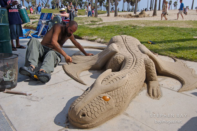 Sculpting a sand dragon. Venice, California, USA.