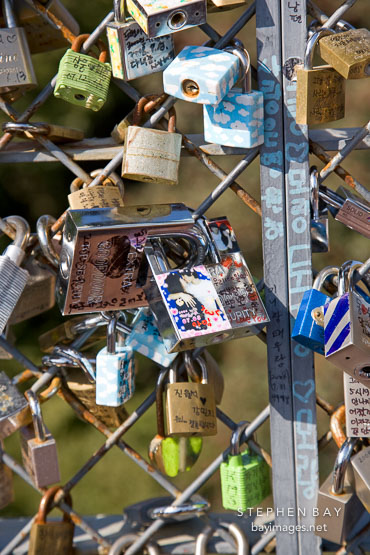 A close-up view of love locks that cover the fences on the outdoor observation decks on N Seoul Tower in Seoul, South Korea. Each lock bears the names of a couple.