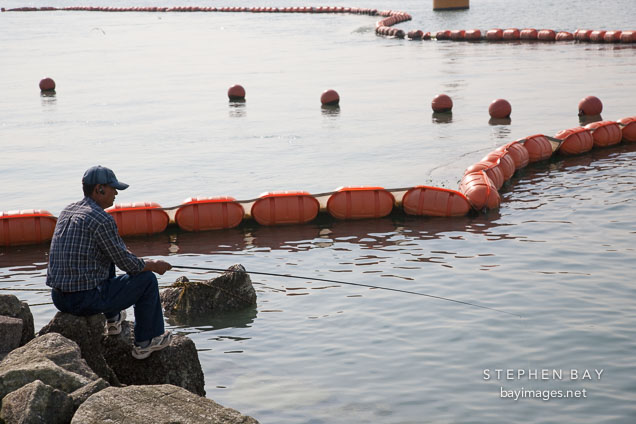 A fisherman perches on the rocks in Wolmido, Incheon, South Korea.