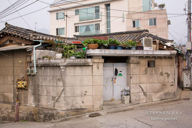 A back door leads from an alley into the courtyard of a traditional Korean home (hanok).
