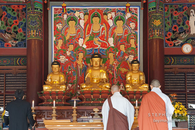 Altar in Daewoongjeon with statues of Sakyamuni Buddha (center) is flanked by Amitabha Buddha and Bhaisagya Buddha. Bongeunsa Temple, Seoul, Korea.