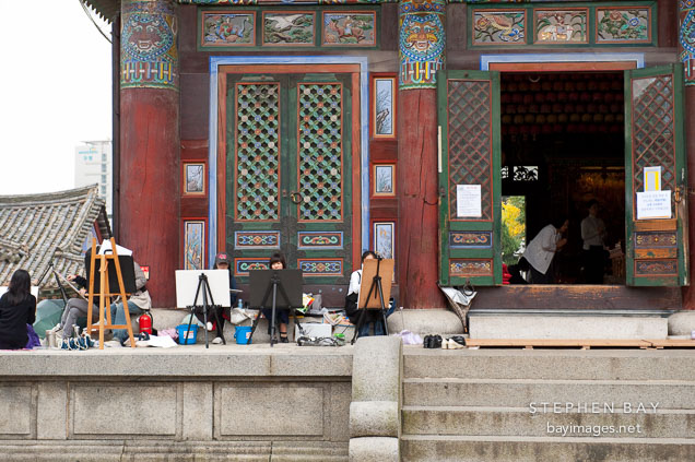 Art students work outside Daewoongjeon, the main temple located at Bongeunsa in Seoul. Daewoong means big hero and is another name for Buddha. The building houses statues of Sakyamuni Buddha, Amitabha Buddha, and Bhaisagya Buddha.