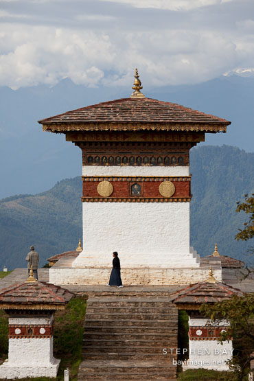 Woman walking around the main chorten at Dochu La pass, Bhutan.