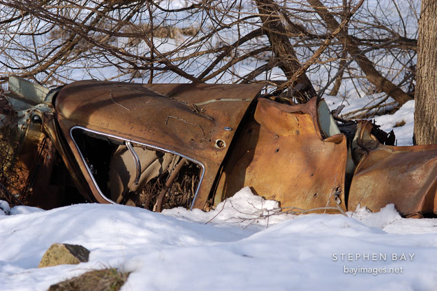 Abandoned car in snowbank. McFarland park. Ames, Iowa.