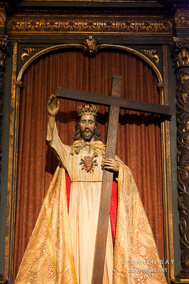 Jesus as king of kings holding cross. Carmel Mission, California.