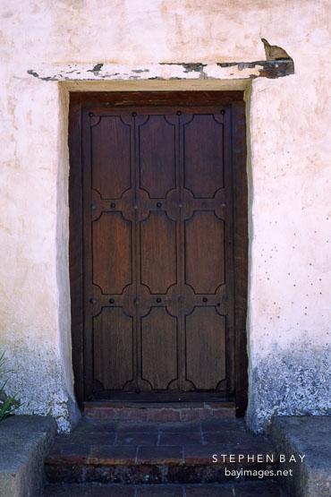 Dark wooden door with no handle or doorknob. Carmel Mission, Carmel, California, USA.