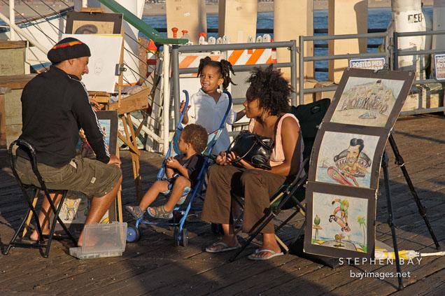 Artist drawing a family portrait. Santa Monica Pier, California, USA.
