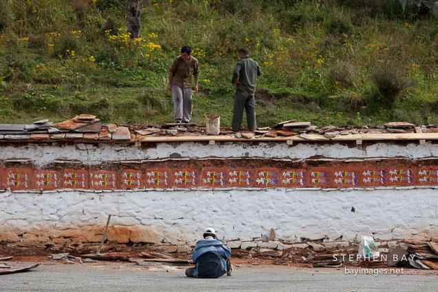Workers repairing mani wall at Dochu La pass, Bhutan.
