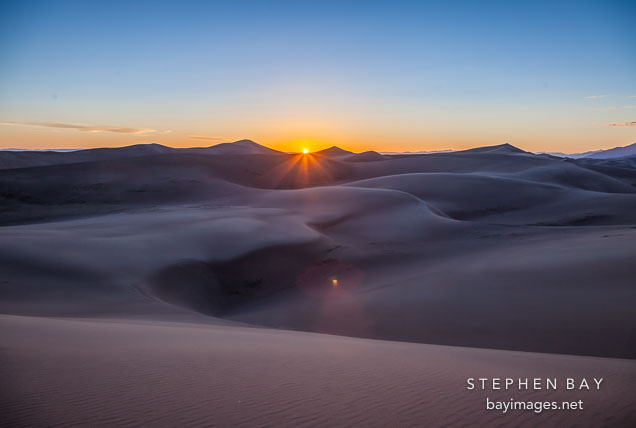 The sun sets behind the dunes. Great Sand Dunes NP, Colorado.