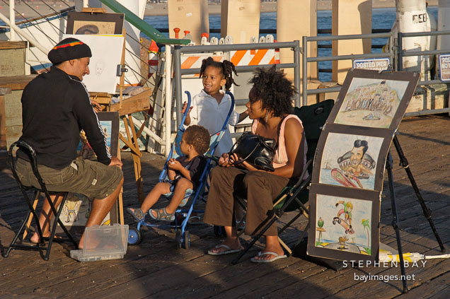Artist drawing a family portrait. Santa Monica Pier, California, USA.