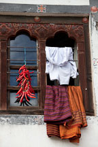 Window with chili peppers and clothes. Thimphu, Bhutan. - Photo #23900