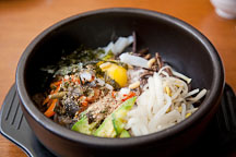 Bibimbap is a popular Korean dish, consisting of a bowl of rice topped with fresh vegetables and sometimes beef and a fried egg. Before eating, diners mix everything together with red chili pepper paste. - Photo #21101
