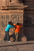 Two boys playing hide and go seek. The Cathedral, Plaza de Armas, Cusco, Peru. - Photo #9296