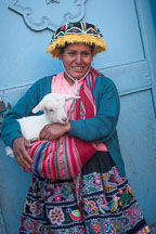 Woman in traditional dress holding baby goat. Pisac market. Sacred Valley, Peru. - Photo #9081