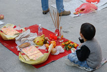 Boy sitting with offering. Wong Tai Sin Temple, Hong Kong, China. - Photo #15713