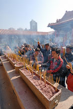 Lighting incense to honor their ancestors. Wong Tai Sin Temple, Hong Kong, China. - Photo #15742