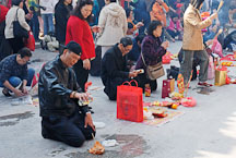 Man offering alcohol and food for the deceased. Wong Tai Sin Temple, Hong Kong, China. - Photo #15718