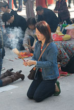 Woman praying with incense sticks. Wong Tai Sin Temple, Hong Kong, China. - Photo #15758