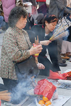 Woman shaking fortune sticks. Wong Tai Sin Temple, Hong Kong, China. - Photo #15685