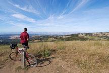 Mountain biker enjoying the view from Borel Hill. Russian Ridge Open Space Preserve. California, USA. - Photo #4318