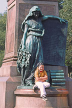 Girl sitting at the statue of the Patron muse of Finnish poetry. Runebergin esplanadi, Helsinki, Finland. - Photo #395