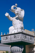 Statue of white elephant standing on rear legs sits atop a column. Hollywood, Los Angeles, California, USA. - Photo #574