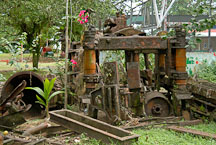 Vegetation grows over abandoned machinery in Tortuguero Village, Costa Rica. - Photo #14002