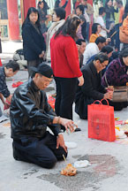 Man pouring alcohol and offering food for the deceased. Wong Tai Sin Temple, Hong Kong, China. - Photo #15720