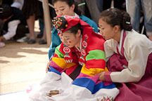 A Korean bride is supported by her friends as she bows as part of this traditional wedding ceremony at the Korean Folk Village. - Photo #20507