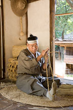 A Korean man weaves sandals from straw. Korean Folk Village, South Korea. - Photo #20556