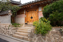 The distinctive traditional Korean hanok (house) features a wooden door, block and beam construction, and a tile roof. - Photo #20913
