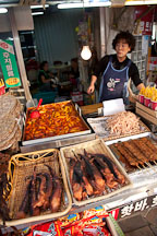 Woman selling tteokbokki (spicy rice cakes), dried squid, and octopus at a food stand.  Incheon, South Korea. - Photo #20144