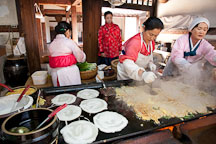 Women cooking Korean pancakes (pajeon) for visitors at the Korean Folk Village. - Photo #20539
