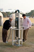 Park goers utilize some of the exercise equipment that can be found in Olympic Park in Seoul, South Korea. - Photo #21683