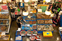 A vendor at the Noryangjin Fish Market in Seoul checks on his wares. - Photo #21188