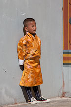 Boy wearing brilliant orange gho. Thimphu tsechu, Bhutan. - Photo #22481
