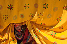 Dancer peering out from the curtains. Thimphu tsechu, Bhutan. - Photo #22621