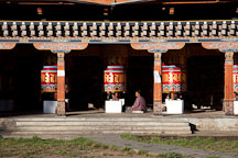 Man sitting by the large prayer wheels at the National Memorial Chorten in Thimphu, Bhutan. - Photo #22880