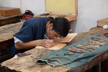 Student drawing design on wood block before carving. National Institute for Zorig Chusum, Thimphu, Bhutan. - Photo #22899