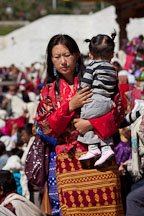 Woman carrying baby at Thimphu tsechu festival. - Photo #22476