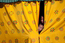 Young boys peeking out of the curtains. Thimphu tsechu, Bhutan. - Photo #22467