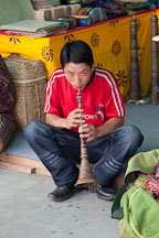 Young man playing the lingm, a traditional Bhutanese flute. Thimphu, Bhutan. - Photo #23899