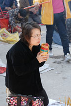 Woman using fortune sticks at Wong Tai Sin Temple. Hong Kong, China. - Photo #15726