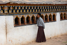 Young girl spinning prayer wheels at Chimi Lhakhang. Lobesa valley, Bhutan. - Photo #23604