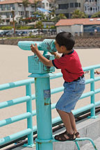 Boy using binoculars. Manhattan Beach, Los Angeles, California, USA. - Photo #7341